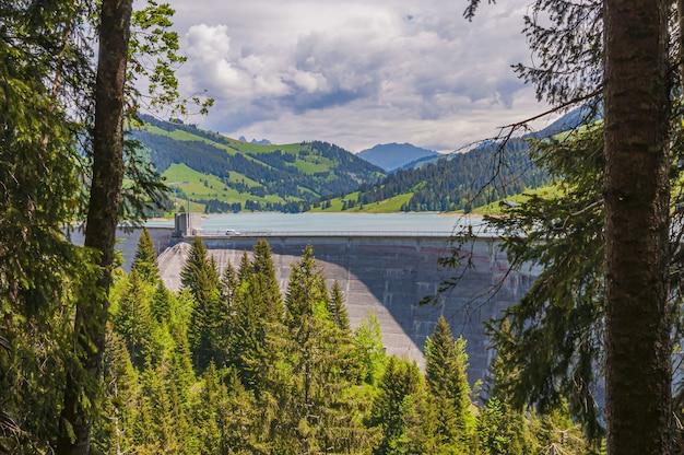 Bela foto da represa lac de l'hongrin com montanhas sob um céu claro - perfeita para um blog de viagens