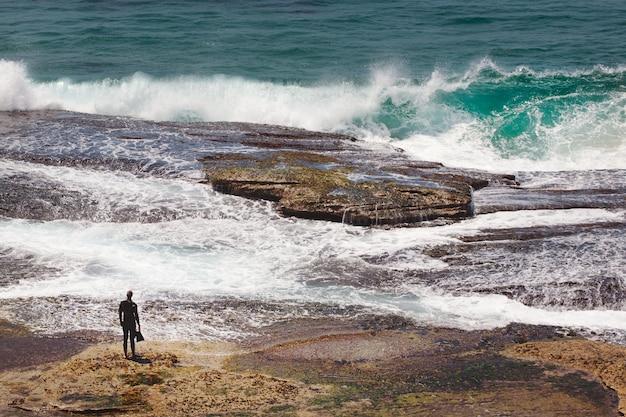 Bela foto da silhueta de uma pessoa em pé em uma rocha perto da praia e olhando para as ondas