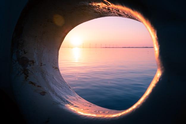 Bela foto da vista de um pôr do sol no mar, visível através de um buraco redondo em um navio