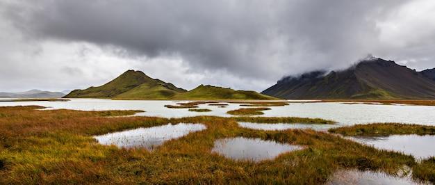 Bela foto das montanhas na região das terras altas da islândia, com um céu nublado e cinza ao fundo