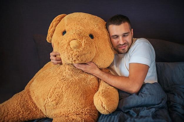 Bela foto de adulto com brinquedo grande urso laranja. guy abraça e se inclina para ele. ele mantém os olhos fechados. o homem descansa. ele está doente.