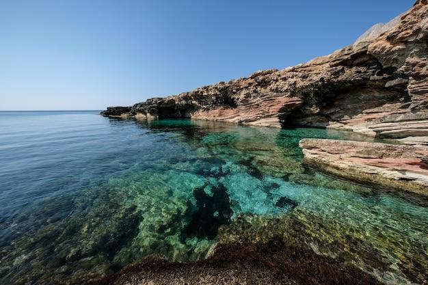 Bela foto de água limpa, perto de um penhasco rochoso em um dia ensolarado
