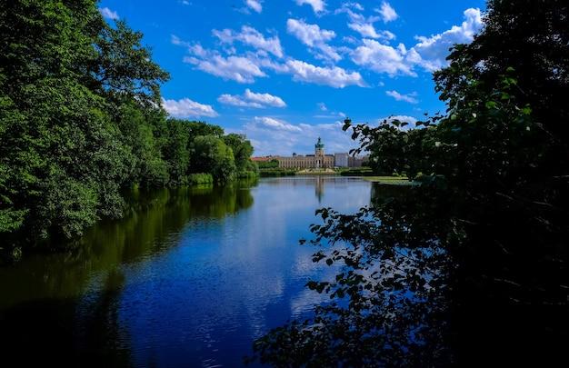 Bela foto de água no meio de árvores e terrenos com construção à distância