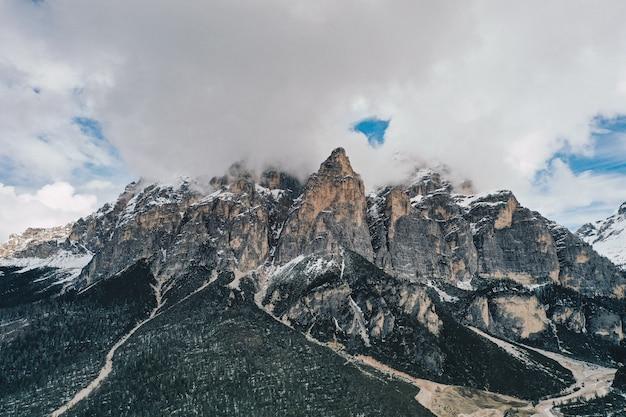 Bela foto de altas montanhas rochosas com nuvens incríveis no céu azul