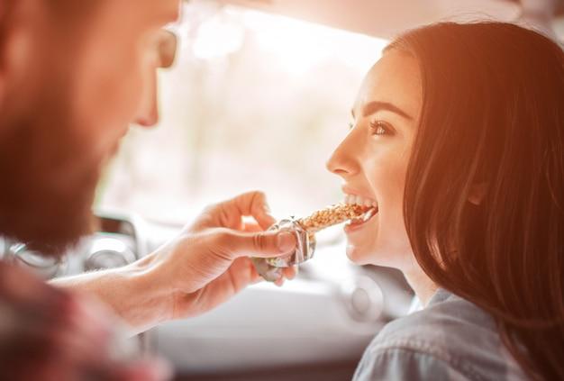 Bela foto de cara alimentando sua namorada com barra de chocolate. ela está mordendo um pedaço e sorrindo.