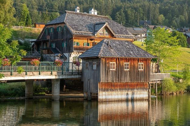 Bela foto de casas de madeira em uma ponte ao lado do rio e das florestas em grundlsee, áustria