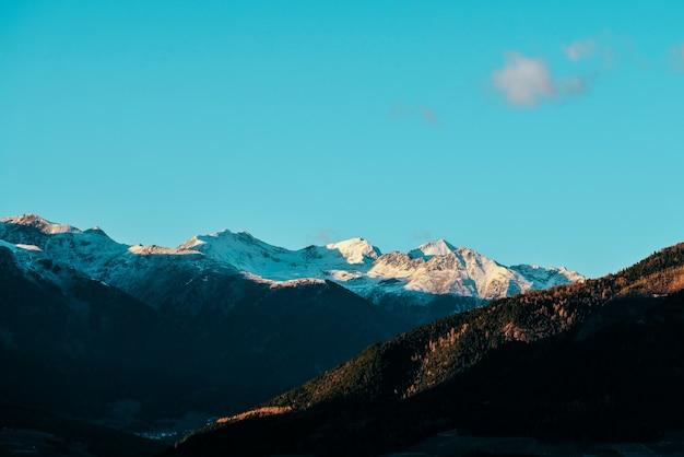 Bela foto de colinas arborizadas e montanhas nevadas ao longe, com céu azul