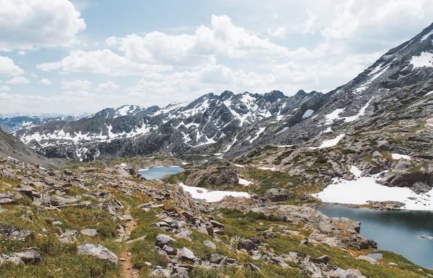 Bela foto de colinas gramadas com pedras e lagoas perto de montanhas sob um céu nublado
