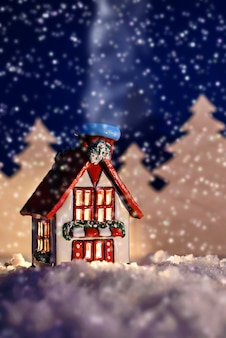 Bela foto de conto de fadas de natal de uma cabana de inverno em uma floresta à noite na neve