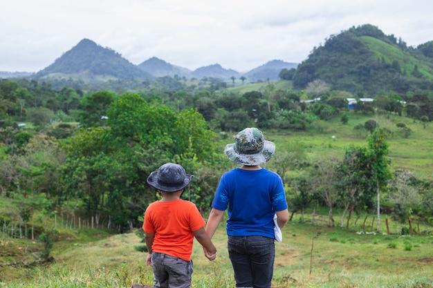 Bela foto de crianças de mãos dadas nas férias na natureza de frente para as colinas e montanhas