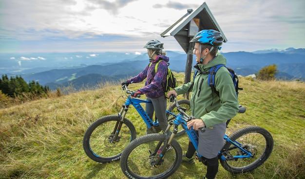 Bela foto de dois ciclistas em pé olhando as maravilhas da natureza
