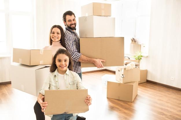 Bela foto de dois pais e uma criança feliz segurando caixas