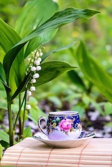 Bela foto de fada verde com uma pequena xícara de chá e lírios do vale no jardim na primavera