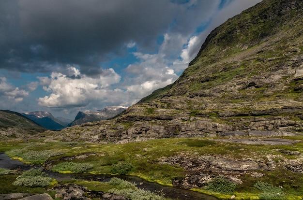 Bela foto de formações rochosas altas cobertas com grama na noruega