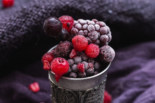 Bela foto de frutas congeladas em uma xícara de prata antiga em um fundo roxo