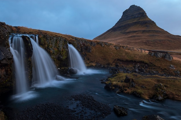 Bela foto de grandes cachoeiras e uma montanha com um céu azul