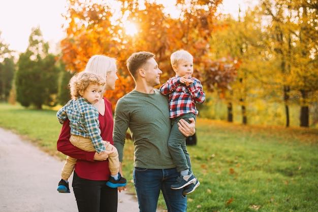 Bela foto de jovens pais e dois pequenos bouys, caminhando no parque