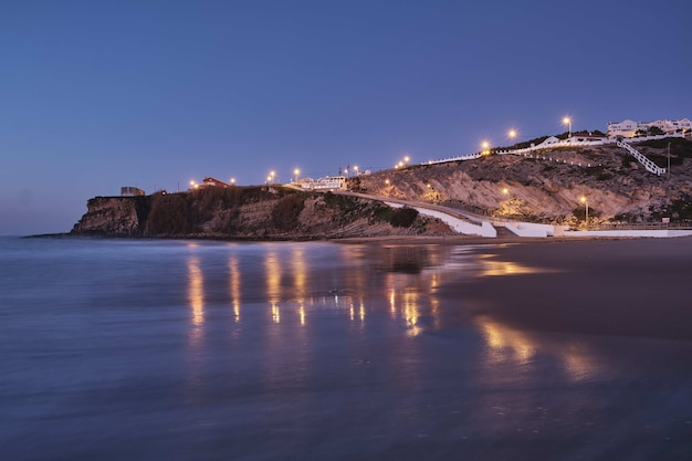 Bela foto de luzes em uma colina rochosa na praia com um céu azul claro