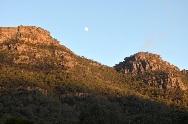 Bela foto de montanhas arborizadas sob um céu claro, com uma lua visível durante o dia