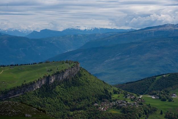 Bela foto de montanhas arborizadas sob um céu nublado