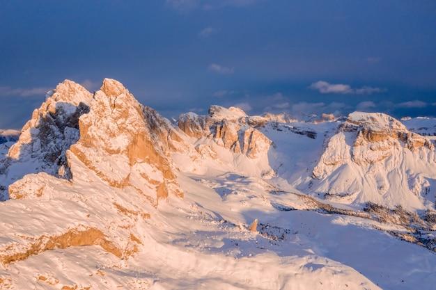 Bela foto de montanhas cobertas de neve ao pôr do sol