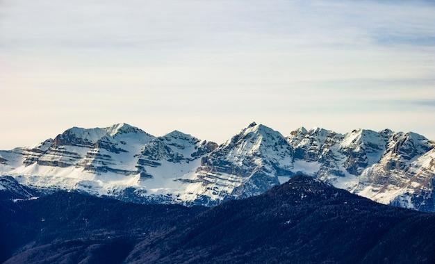 Bela foto de montanhas cobertas de neve em um dia ensolarado com céu claro ao fundo