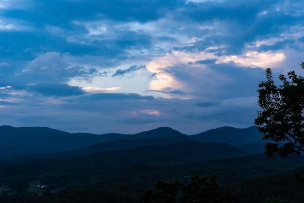 Bela foto de montanhas e colinas com nuvens de tirar o fôlego no céu