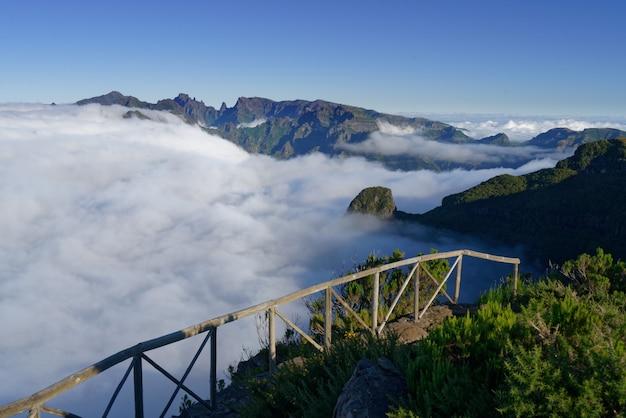 Bela foto de montanhas e colinas verdes cobertas por nuvens brancas em um céu claro