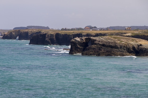 Bela foto de montanhas rochosas banhadas pelas ondas azuis do oceano