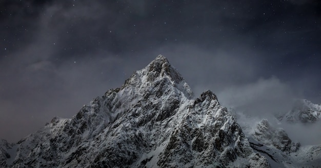 Bela foto de montanhas rochosas cobertas de neve branca