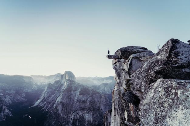 Bela foto de montanhas rochosas com uma pessoa de pé na beira