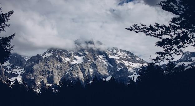 Bela foto de montanhas rochosas e nevadas com incríveis nuvens e vegetação ao redor