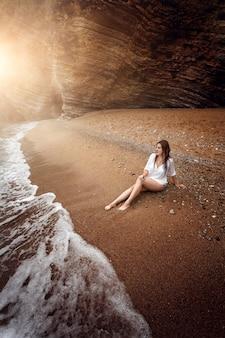 Bela foto de mulher sexy relaxando em uma praia deserta ao pôr do sol