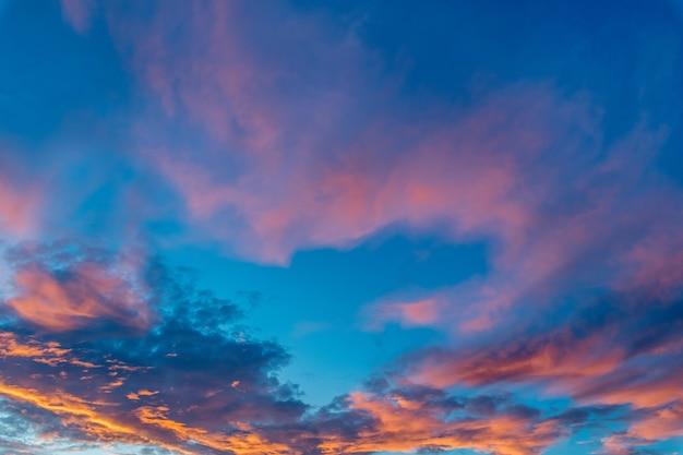 Bela foto de nuvens cor de rosa em um céu azul claro com um cenário do nascer do sol