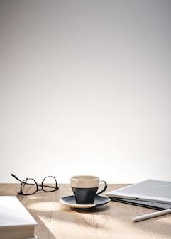 Bela foto de óculos ópticos e uma xícara em uma mesa com um fundo branco e espaço para texto
