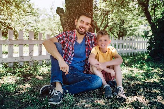 Bela foto de pai e filho sentados juntos debaixo da árvore e olhando na câmera. eles estão sorrindo. adulto está abraçando criança.
