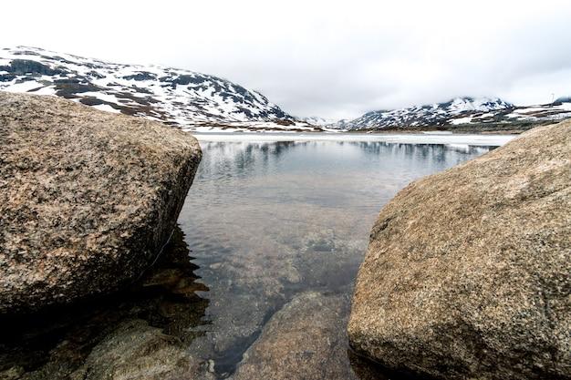 Bela foto de pedras à beira do rio e montanha nevada na noruega