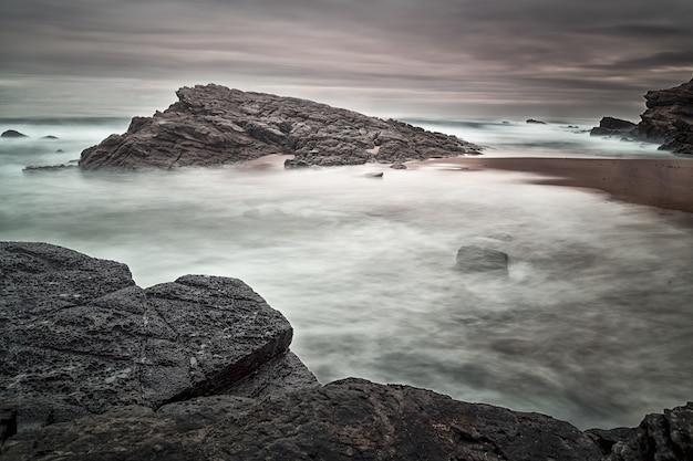 Bela foto de pedras à beira-mar com um céu sombrio no