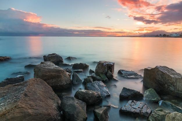 Bela foto de pedras à beira-mar durante o pôr do sol