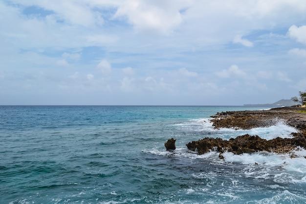 Bela foto de pedras em uma praia com um céu azul nublado