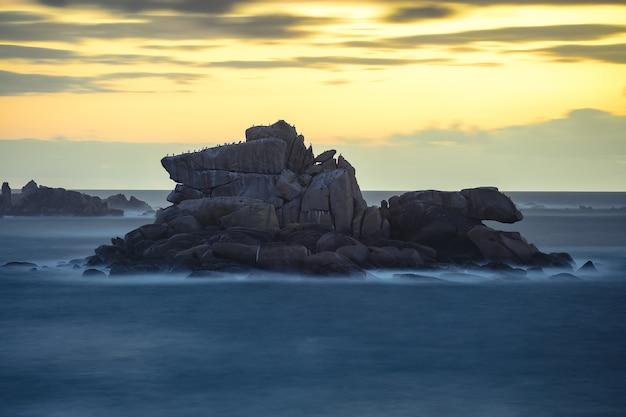 Bela foto de pedras em uma praia durante o pôr do sol