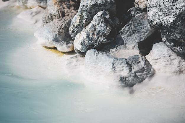 Bela foto de pedras empilhadas perto de uma água cristalina