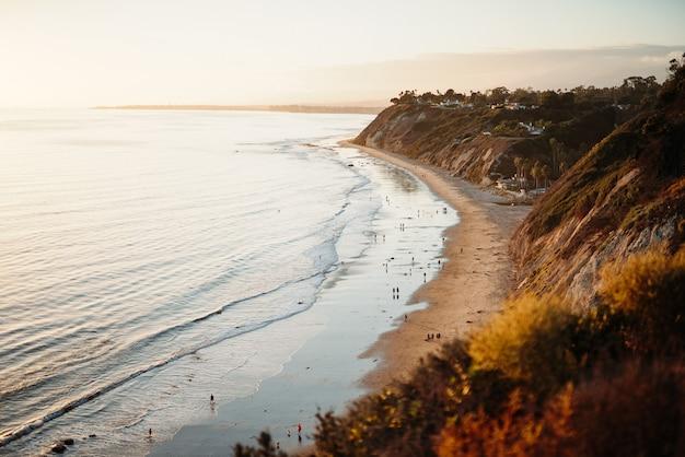 Bela foto de pessoas caminhando em uma praia selvagem ao lado de colinas baixas