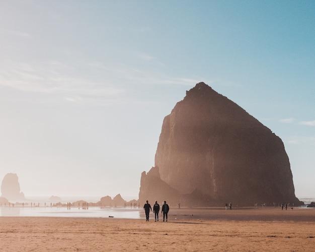 Bela foto de pessoas caminhando na praia com uma pedra à distância durante o dia