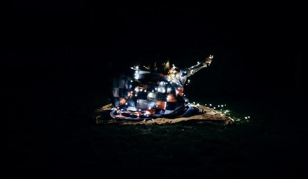 Bela foto de pessoas envolvidas em um cobertor e luzes de fadas brancas na escuridão