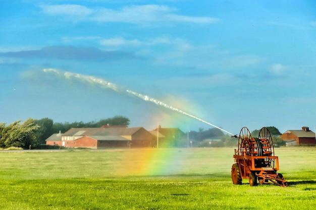 Bela foto de um arco-íris se formando de irrigadores de água