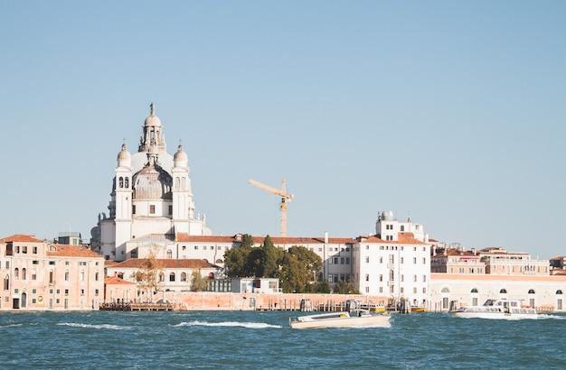 Bela foto de um barco na água e um edifício à distância nos canais de veneza na itália