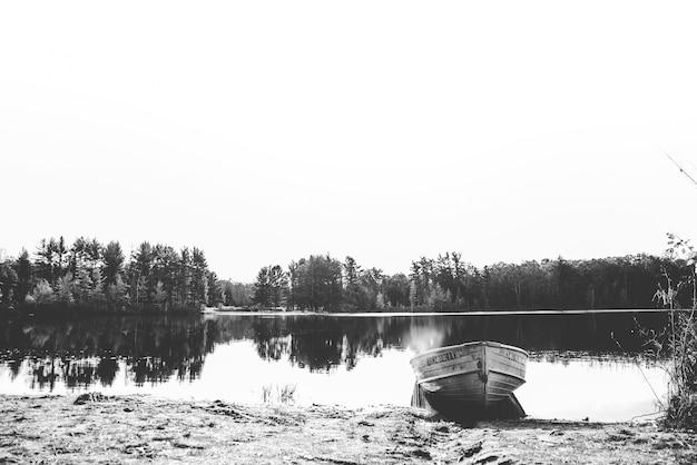 Bela foto de um barco na água perto da costa, com árvores à distância em preto e branco