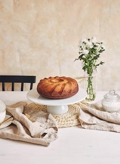 Bela foto de um bolo delicioso colocado em um prato branco e uma flor branca perto dele