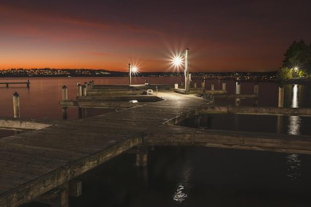Bela foto de um cais de madeira iluminado no lago ao redor da cidade à noite